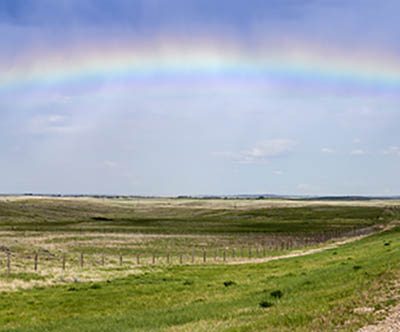 Rainbow over the highway in Saskatchewan. Saskatchewan, Canada.